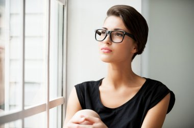 Short hair woman sitting on window sill