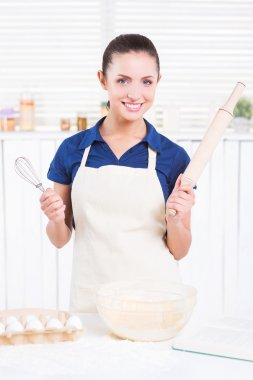 Woman in apron holding rolling pin and wire whisk