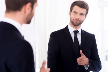 Man in suit standing against mirror