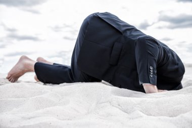 Man in formal wear hiding his head in sand