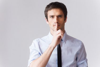 Man in white shirt holding finger on lips