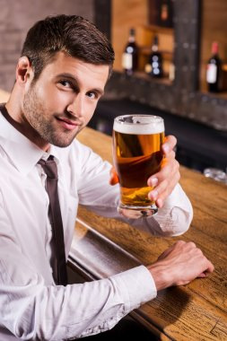 Man in shirt and tie toasting with beer