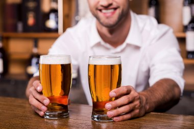 Bartender stretching out glasses with beer
