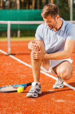 Tennis player touching his knee and grimacing