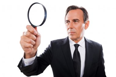 Concentrated businessman looking through magnifying glass