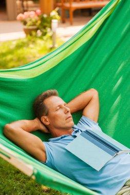 Mature man sleeping  in hammock