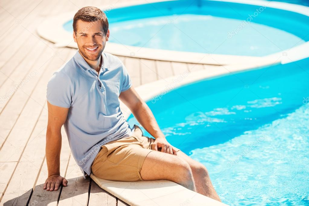 Man in polo shirt sitting by the pool stock photo for Pool man show