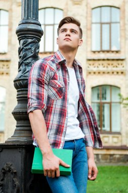 Thinking about a bright future. Low angle view of thoughtful male student holding book and looking up while standing against university building stock vector