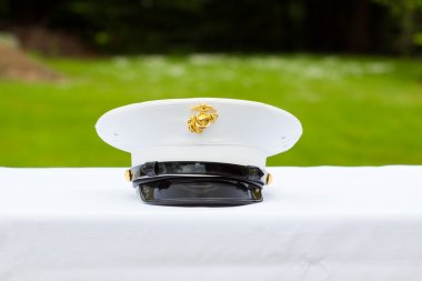 A marines hat off his head while at a wedding in uniform for armed forces soldiers and family.