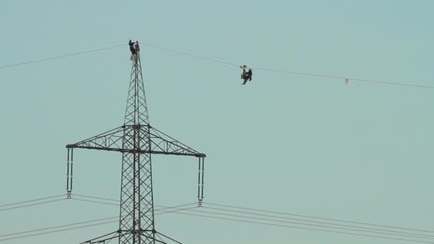 silueta dvou techniků pracuje na nové přenosové vedení