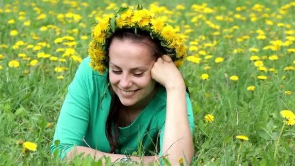 Young beautiful girl lying in a field of dandelions