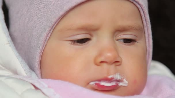 A cute little baby eating with of spoon.A cute little baby reluctantly eats baby food.