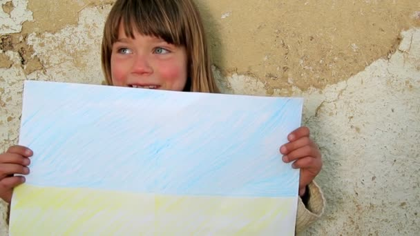 Boy holding a sheet of paper.Child holding a sheet of paper.Against the background of an old wall