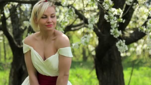 Young beautiful girl posing at the camera in the flowering spring garden,Beautiful girl in spring garden,Beautiful young woman enjoying in spring garden