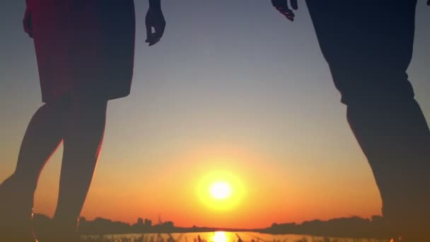 Young couple in love kissing on the lake at sunset, romantic date, gently kiss each other, looking at each other