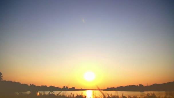 Mladý pár v lásce líbání na jezeře v západu slunce, romantický datum, něžně políbit navzájem, při pohledu na sebe
