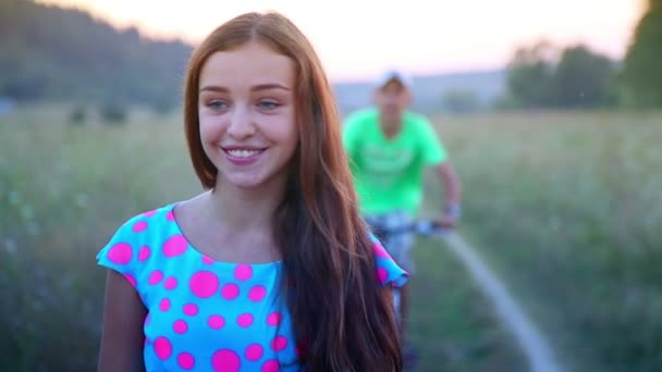 Young, beautiful, cheerful girl shyly looks at adolescent boys.