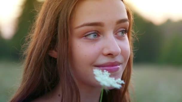 mladá, krásná, veselá dívka se stydlivě dívá na dospívající chlapce