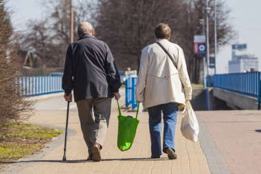 Old Couple Walking with Shopping Bags