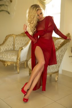 Blonde beautiful woman posing in red dress.