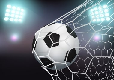 Soccer ball in the goal net on stadium with light