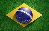Soccer ball with brazilian flag on soccer field