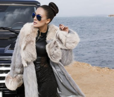 sexy glamour woman in fur coat posing beside a car
