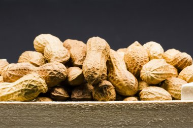 Peanuts in shell in a wooden box, with black background