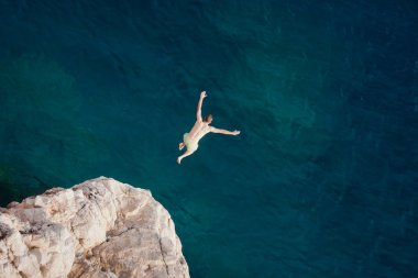 Young man jumping from cliff into sea