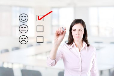 Hand putting check mark with red marker on customer service evaluation form. Office background.