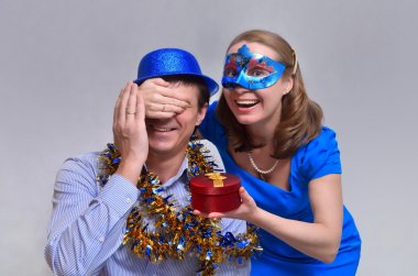 Woman in mask does surprise and wishes Happy New Year man masquerade with hat