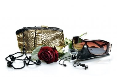 Womanish handbag, accessories, sun glasses and a red rose