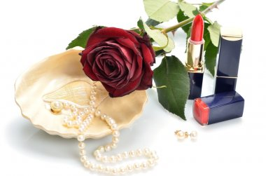 Items for decorative cosmetics, makeup, pearl necklace in the sink and red flower