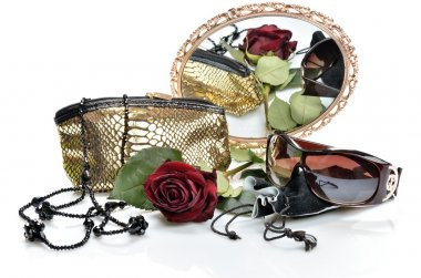 Women's handbag, accessories, sunglasses and a red rose are seen in the mirror