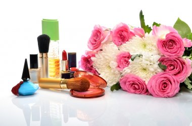 Women's jewelry, perfumes, cosmetics and a bouquet of flowers in still life