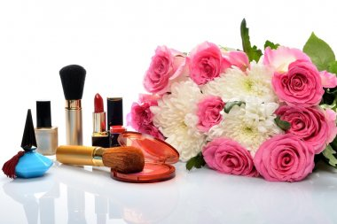 Decorative cosmetics and perfumes subject against a beautiful bouquet of flowers
