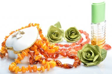Women's jeweler ornaments - necklace perfumes and flowers in still life