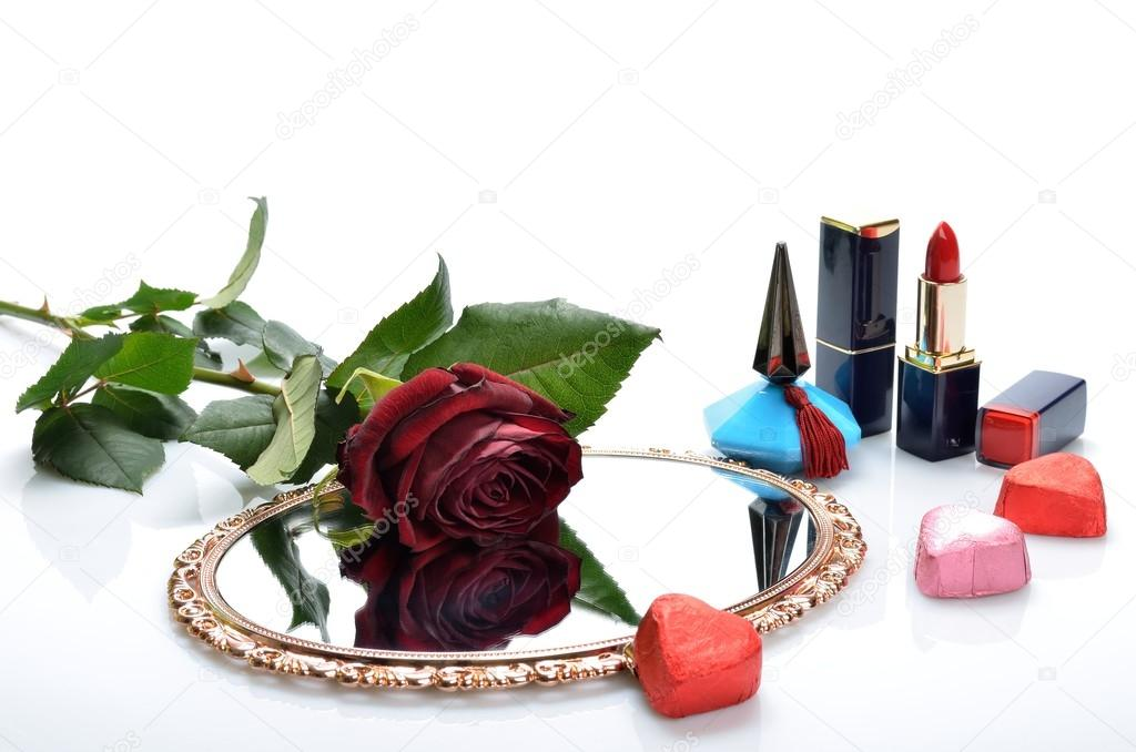 Perfume, lipstick, mirror candy hearts and a red rose in a still life