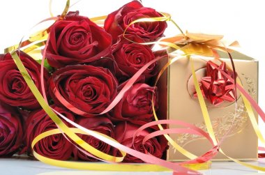 Golden gift box and a bouquet of red roses in a still life
