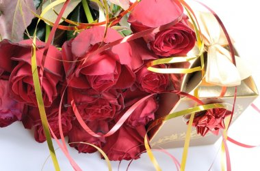Golden gift box and a bouquet of red roses