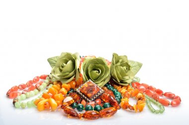 Women's jewelry - different colored beads, brooch and flowers roses in still life