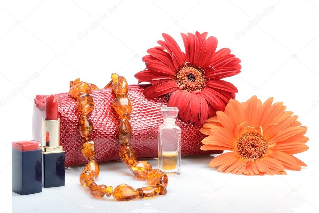 Gerbera flowers, cosmetics, perfumery and cosmetic bag female beads in still life