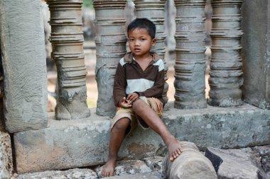 A shy boy sitting on a stone pillar
