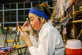 Hong Kong, China - August 18, 2014: A traditional opera actor is making up at the back stage of a traditional tea house. Generally, an actor needs 30 - 60 minutes to complete the whole process.