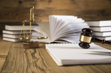 Wooden gavel, Lady Justice, gold scale and law books on wooden table