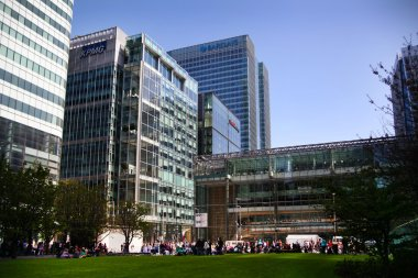 LONDON, CANARY WHARF UK - APRIL 13, 2014 - Modern glass architecture of Canary Wharf business aria, headquarters for banks, insurance, media and other world known companies Local park view