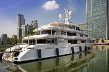 LONDON UK - MAY 7, 2014: Private yacht based in Canary Wharf, against modern glass skyscrapers