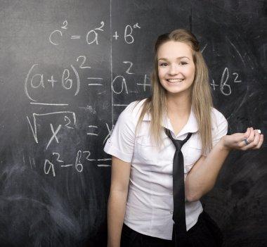 Portrait of pretty cute student with book near blackboard