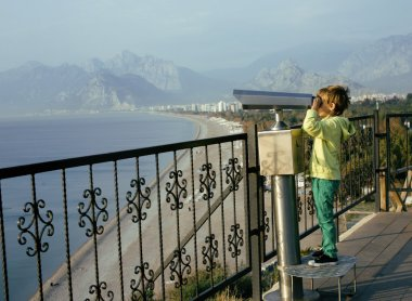 Little cute boy looking through telescope at sea viewpoint