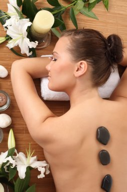 spa. picture of woman in spa salon with hot stones